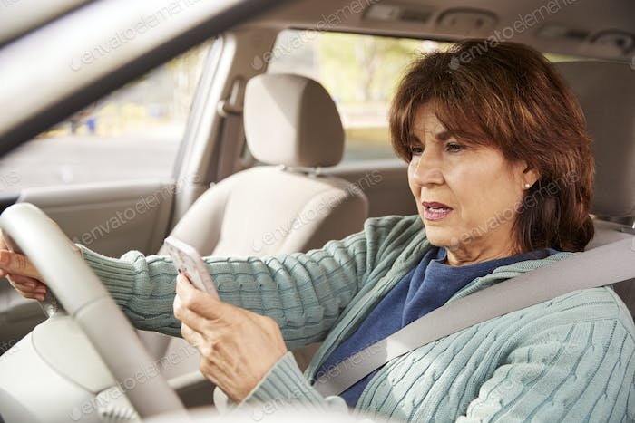 Senior woman in car checking her smartphone while driving