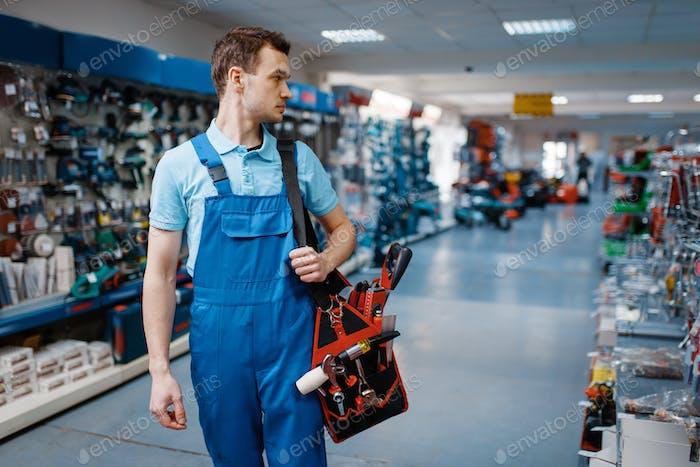Männliche Arbeiter in Uniform hält Werkzeugkoffer im Werkzeugladen
