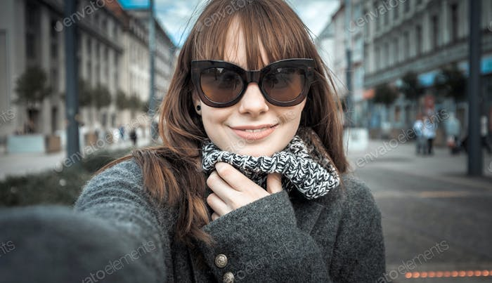 Smiling pretty woman selfie portrait at the city