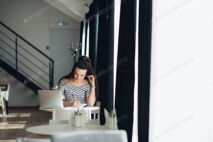 Happy woman writing in a notebook. Adult female sitting at the table near window with a laptop.