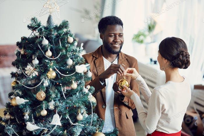 Elegant Mixed-Race Couple Decorating Christmas Tree