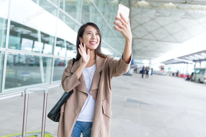 Happy woman taking selfie by smart phone in airport