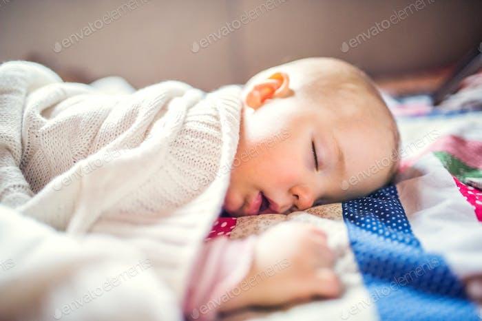 Ein Kleinkind Mädchen, das zu Hause auf einem Bett schläft.