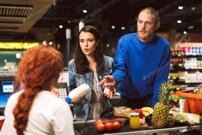 Junge nachdenkliche Mann und Frau mit Milch der Flasche in der Hand emoti