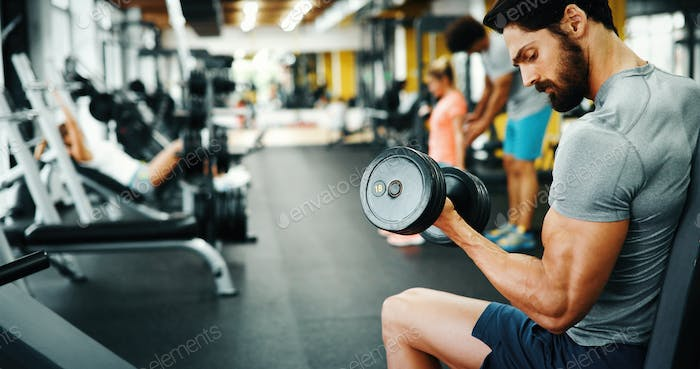 Determined handsome and young male working out in gym