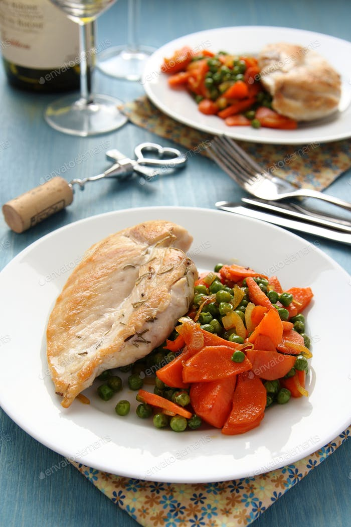 Roast chicken breast with vegetables on white plate