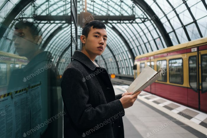 Young Asian man with newspaper confidently looking in camera waiting for train at railway station