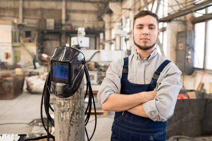 Purposeful handsome welder in factory workshop