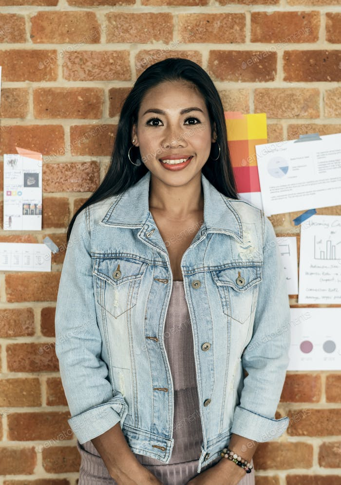 Portrait of Asian woman with brick wall