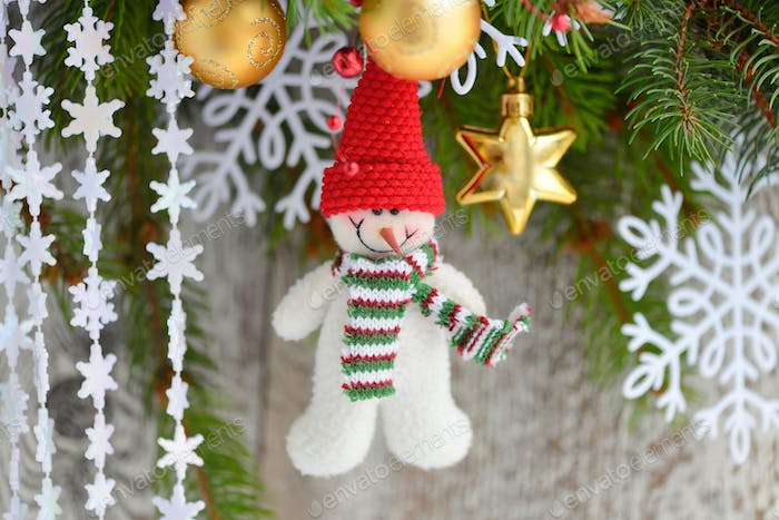 Snowman with Christmas ornaments on the branches of spruce
