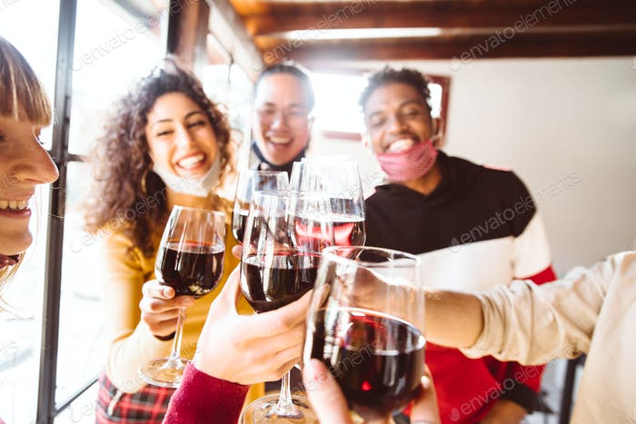 Happy friends wearing protective face masks toasting red wine at restaurant