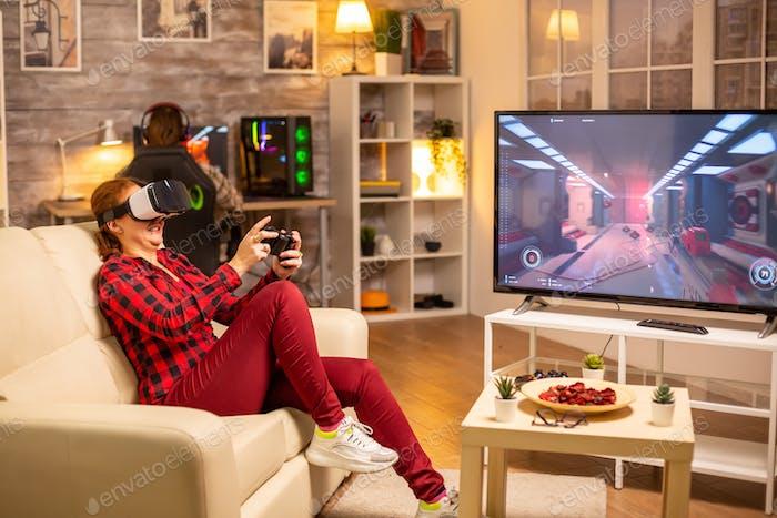 Женщина-геймер играет в видео игры с помощью гарнитуры VR поздно ночью