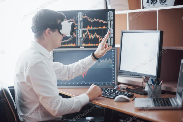 Businessman in virtual reality trading on stock market. Multiple computer screens ful of charts and