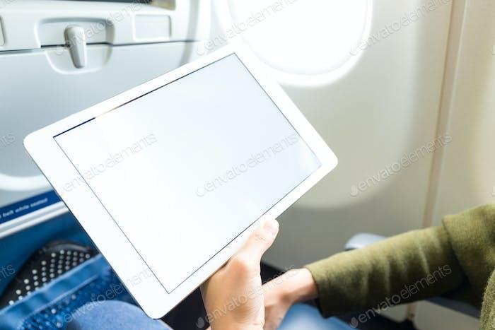 Junge Frau mit Tablette im Flugzeug