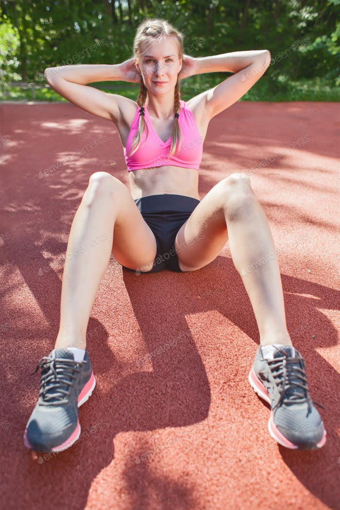 young smiling sportswoman in sportswear doing abs exercise