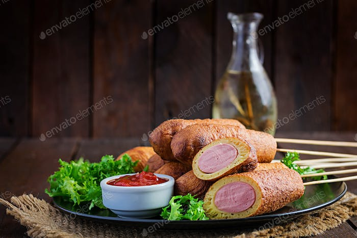 Traditional American corn dogs with mustard and ketchup on black plate. Street food. Copy space