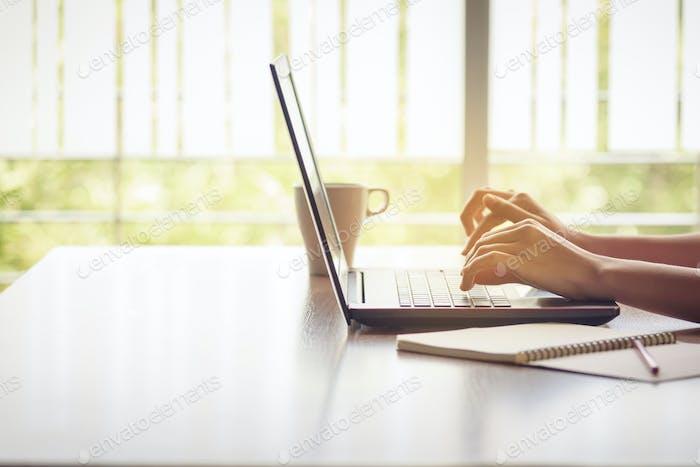 Hände Tippen auf Laptop auf dem Schreibtisch, Geschäft bei der Arbeit