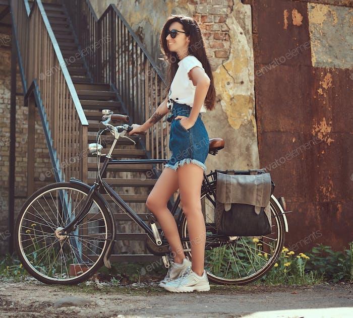 Slim modisches Mädchen posiert mit Fahrrad in der Nähe eines alten Gebäudes.