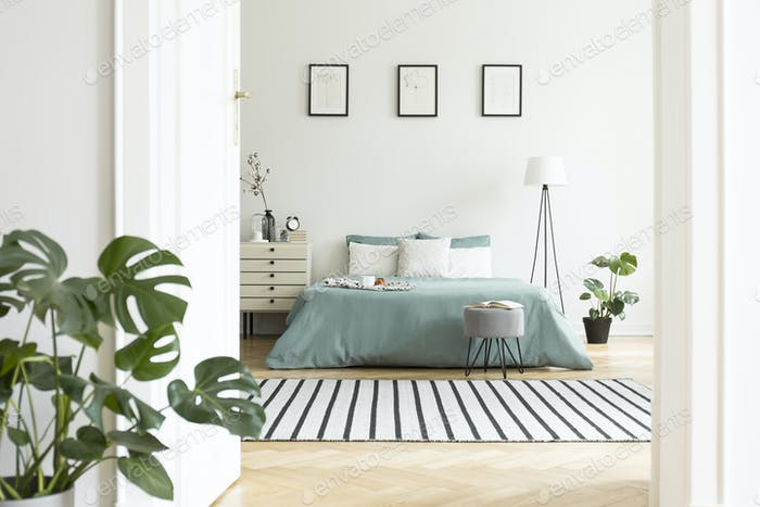 Posters above green bed in white bedroom interior with plants an photo by  bialasiewicz on Envato Elements