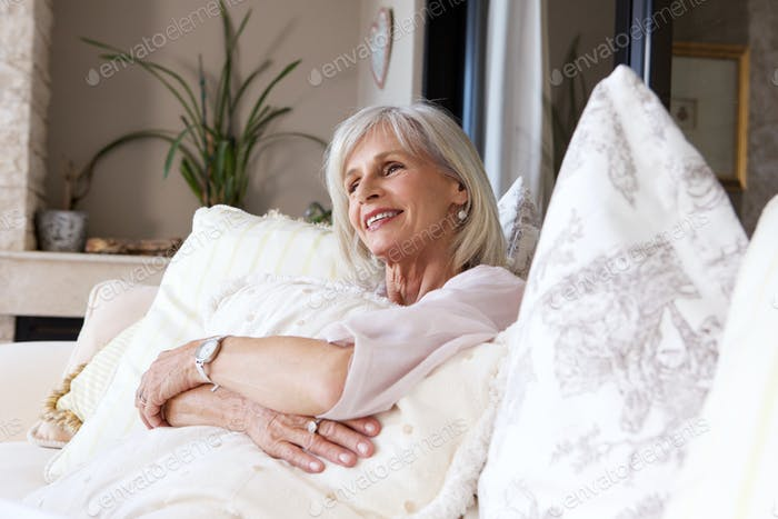 happy older woman sitting on couch relaxed
