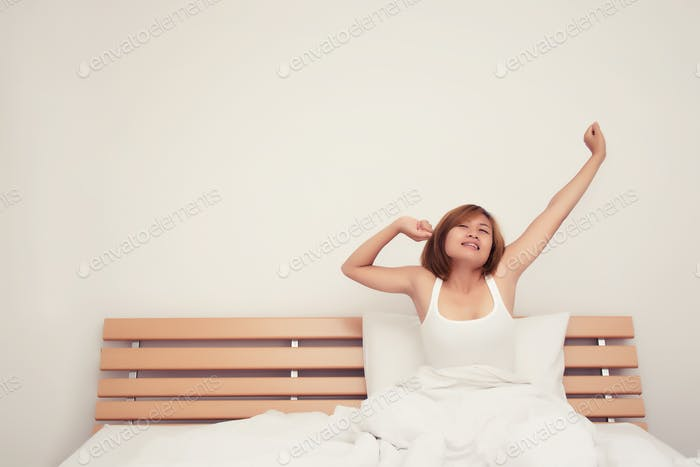 Beautiful young woman stretching on bed after wake up in the morning