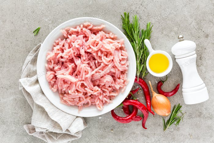 Mince. Ground meat with ingredients for cooking on light grey background. Top view