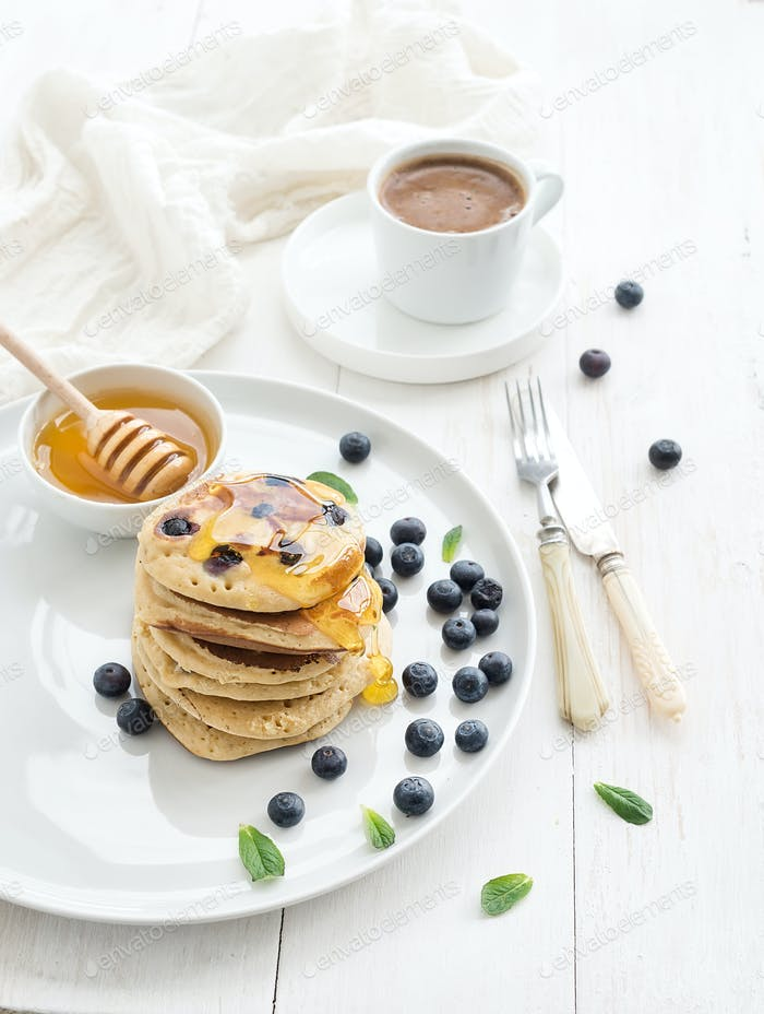 Breakfast set. Blueberry pancakes with fresh berries, honey, mint leaves and cup of coffee