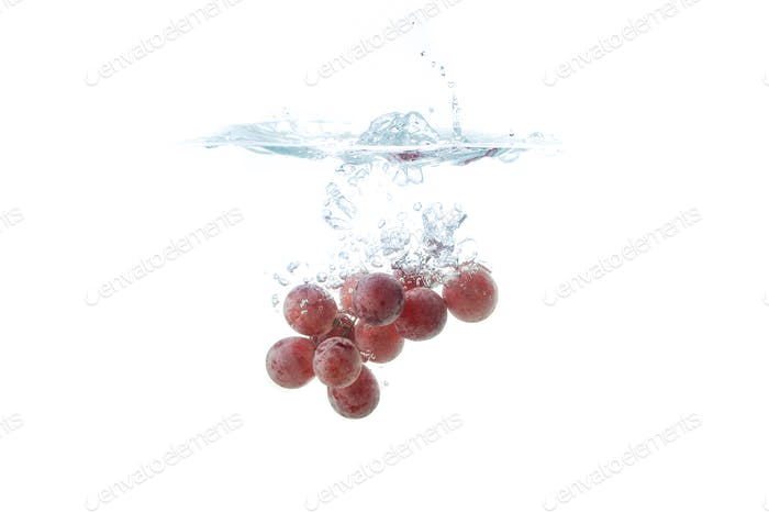 Isolated Red grapes splashing and sinking in water on white background with air bubbles