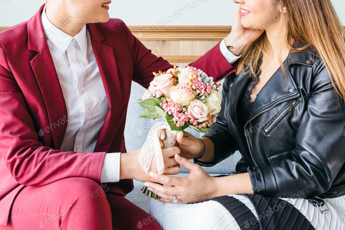 Tender lesbian couple posing with bouquet