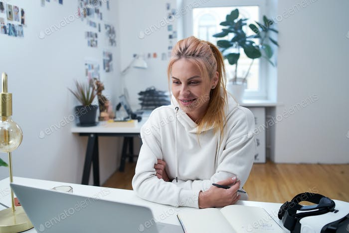 Joyful female freelancer looks at laptop sitting at table in office