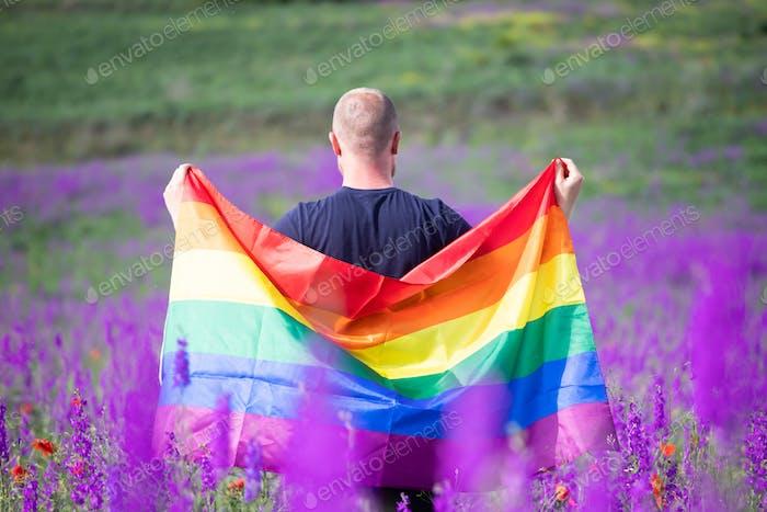 Junger Mann mit LGBT-Flagge.