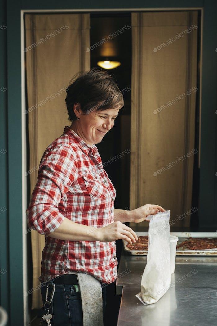 Eine Frau, die in einer kommerziell Küche arbeitet und Pfannkuchen macht.