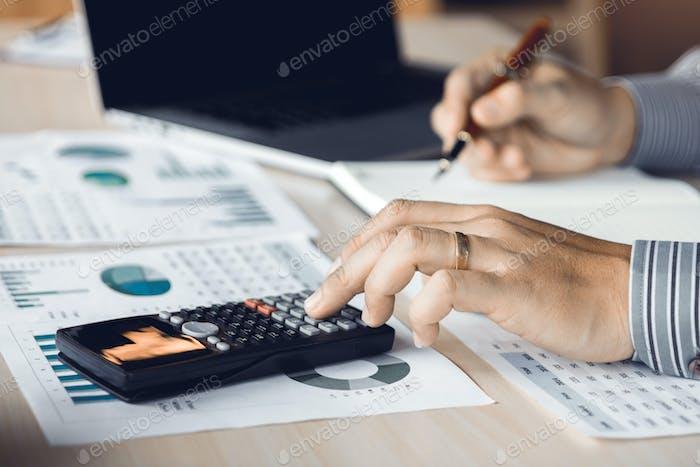 Contador de empresario presionando calculadora y haciendo cálculos en la mesa.