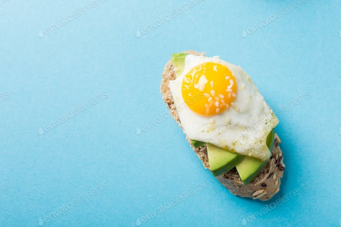 Healthy sandwich with fresh avocado and fried quail eggs