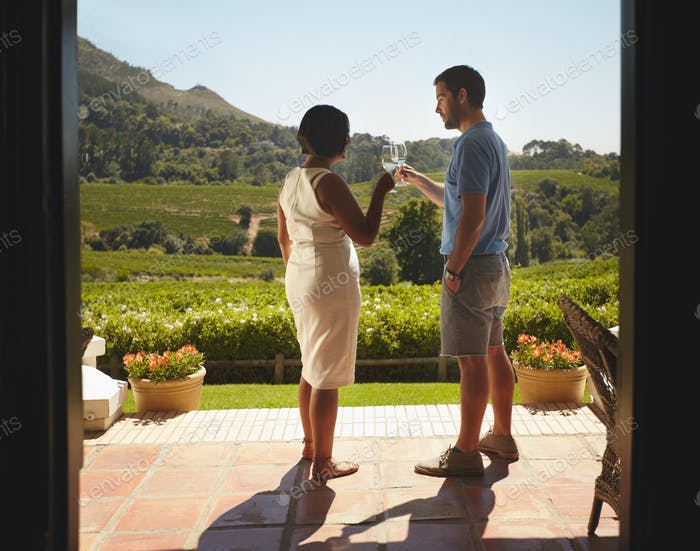 Young couple on vacation celebrating with wine