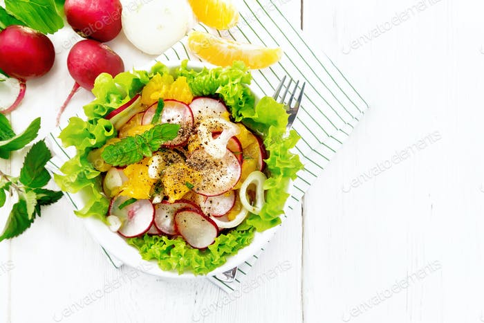 Salad of radish and orange with mint on board top