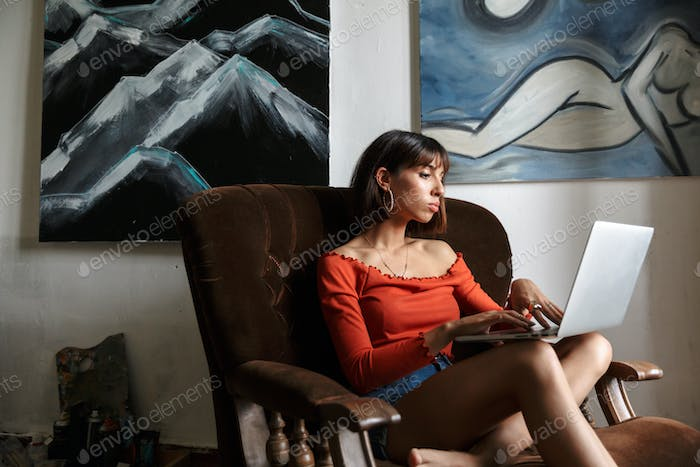 Beautiful young woman artist sitting in the art studio