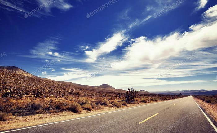 Vintage stylized picture of a Death Valley deserted road, USA.