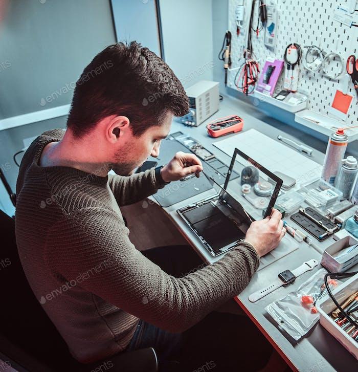Der Techniker repariert einen defekten Tablet-Computer in einer Werkstatt