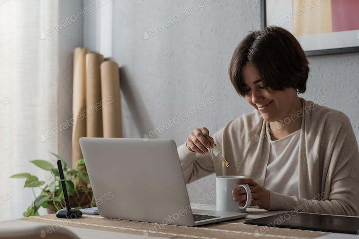 Cbd hemp - Woman taking cannabidiol oil in tea cup while working at home office - Focus on dropper