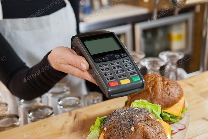 Nahaufnahme des Besitzers, der Kreditkartenleser hält
