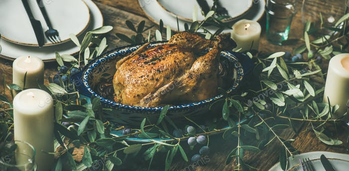 Whole roasted chicken for Christmas, plates and candles