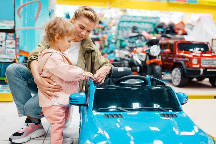 Mother with girl choosing electromobile in store