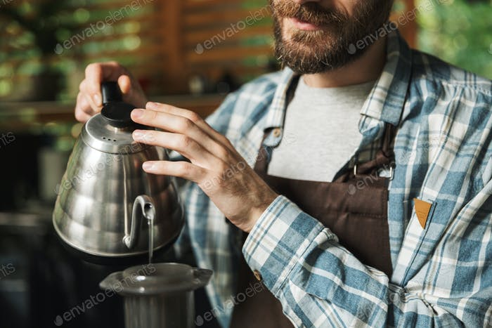 Portrait of young barista man making coffee while working in str