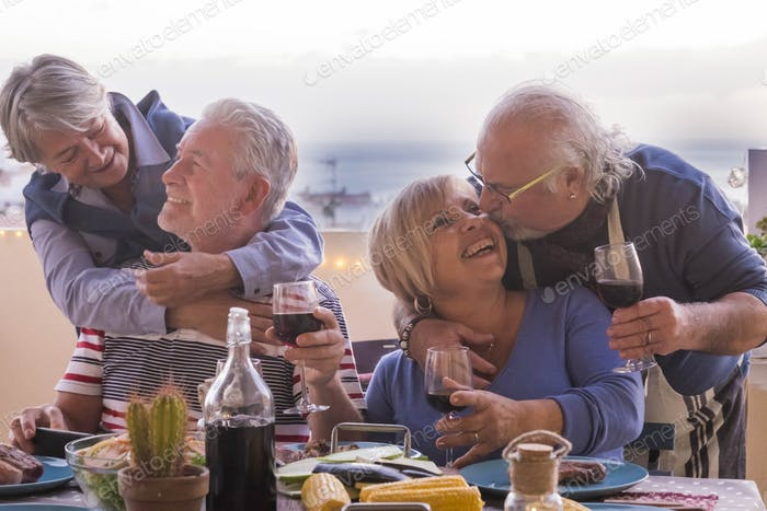 two mature couple stay together with love smiles and kisses