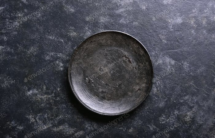 Empty black plate over stone background