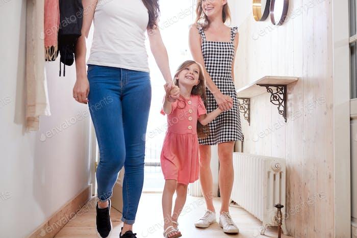 Blick im Flur Wie Gleiches Geschlecht Weibliches Paar Mit Tochter Öffnen Vordertür Von Zu Hause