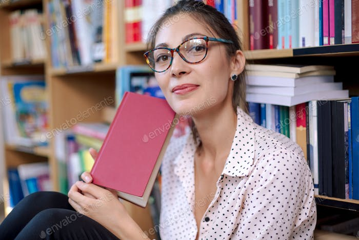 Beautiful woman with glasses and book in a book shop