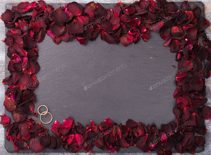 Background of red rose petals and wedding rings.