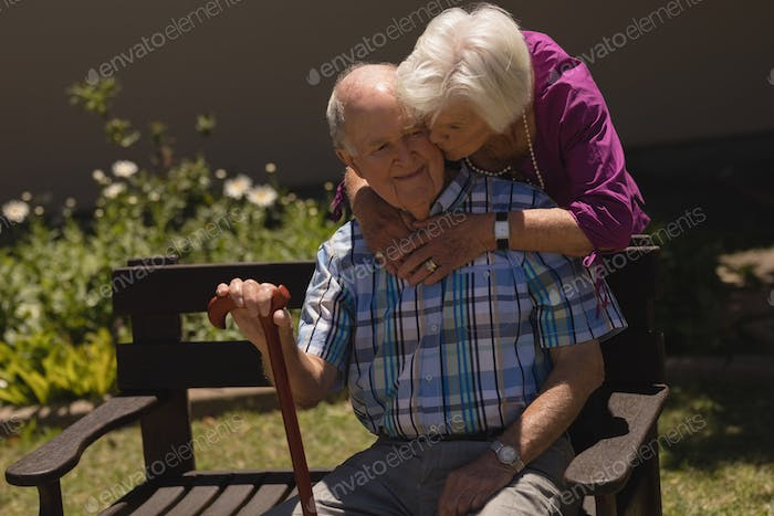 Front view of romantic senior woman embracing and kissing happy senior man in garden on sunny day